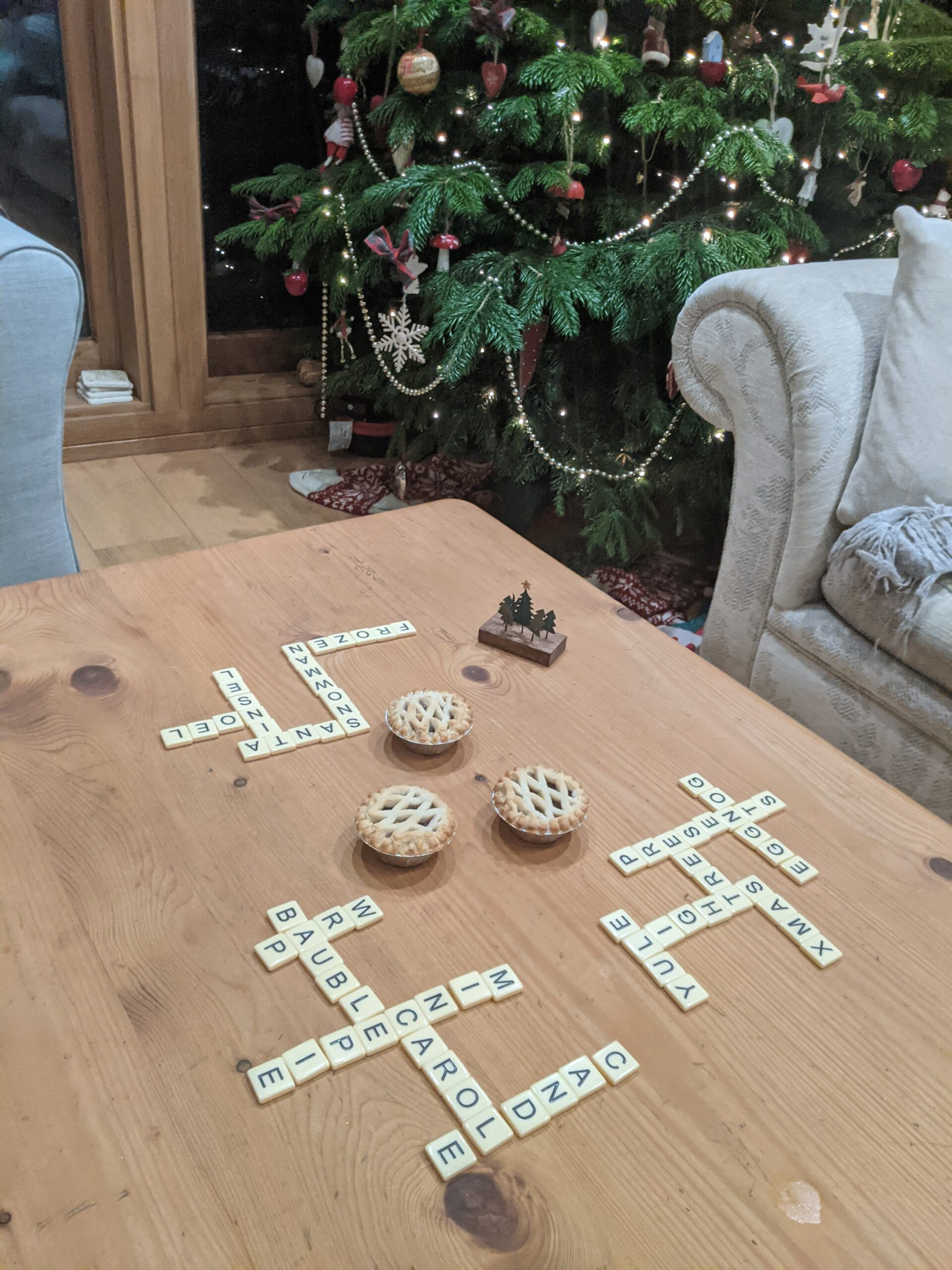 Coffe table with tiles spelling out christmas themed words, christmas tree in the back ground.